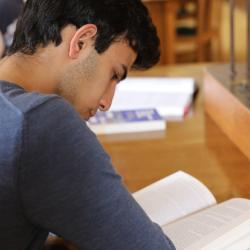 A student reads a book in a library