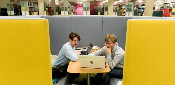 Two students in a library looking at a laptop